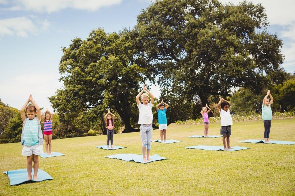 Enfants en séance de yoga dans un parc | Dynamite Moov